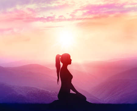 sport silhouette: Silhouette of a woman practicing yoga in the mountains at sunrise Stock Photo