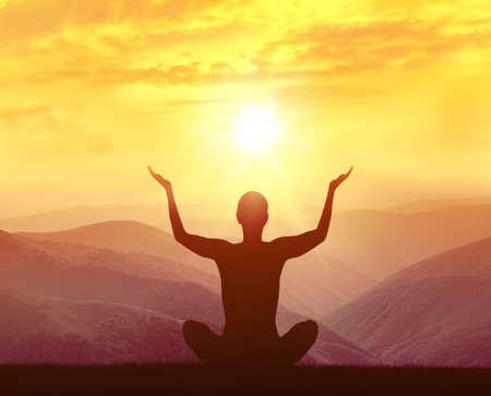 human energy: Silhouette of a woman practicing yoga in the mountains at sunrise Stock Photo