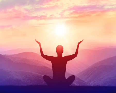 mind body soul: Silhouette of a woman practicing yoga in the mountains at sunrise Stock Photo