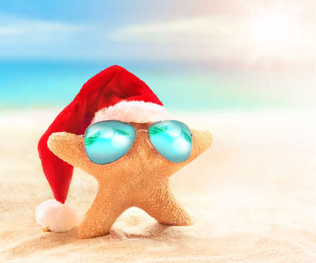 yule tide: starfish in santa hat and sunglasses on the sunny beach