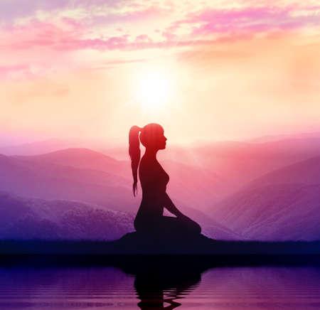 Yoga en meditatie. Silhouet van de vrouw in de berg Stockfoto
