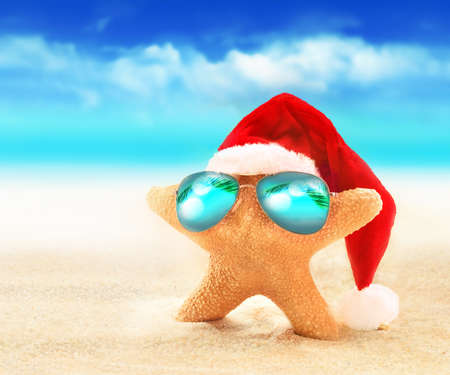 Starfish in zonnebril op de zomer strand en kerstmuts. Kerstmis. Stockfoto
