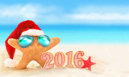 Starfish in sunglasses on summer beach and santa hat. Christmas. Imagens