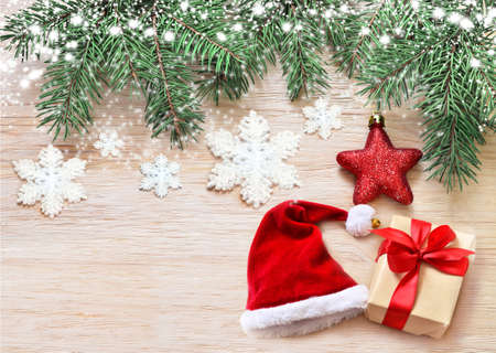 holiday background: Christmas wooden background. Pine, hat and star on the wooden background. Stock Photo