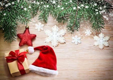 decoration: Christmas wooden background. Pine, hat and star on the wooden background. Stock Photo