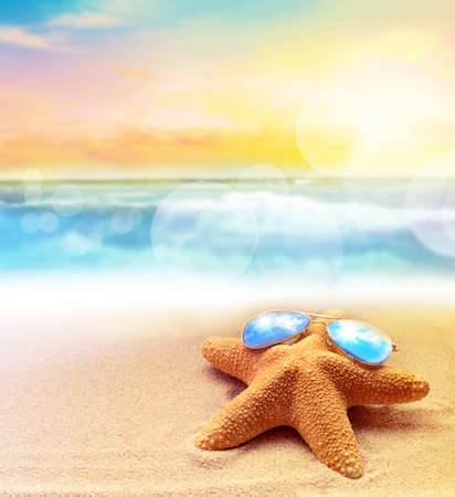 Starfish in blue sunglasses on the summer beach