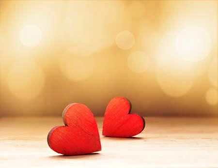 Close-up van twee rode houten harten tegen defocused lichten.