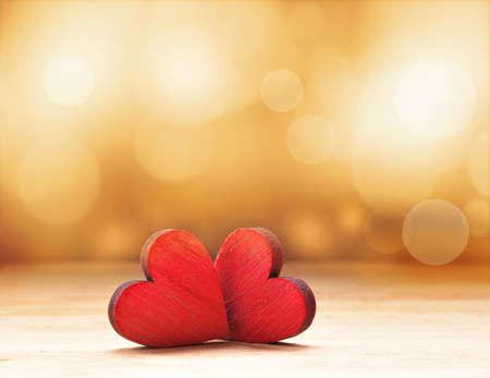romance: Close up de dois corações de madeira vermelhos contra luzes desfocadas. Imagens