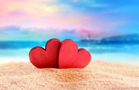 Twee houten rode harten op de zomer strand Stockfoto