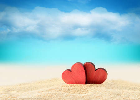 dia soleado: Dos corazones rojos de madera en la playa verano Foto de archivo