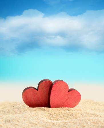 Twee houten rode harten op het strand van de zomer