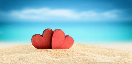 Two wooden red hearts on the summer beach