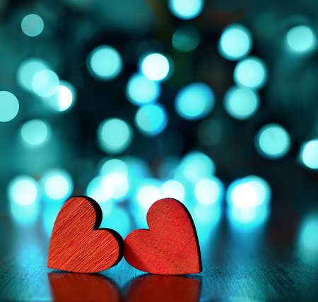 Two red wooden hearts against defocused lights.