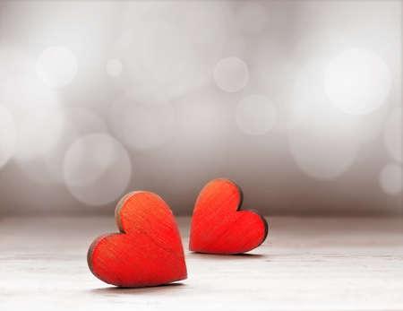 Twee rode houten harten tegen defocused lichten. Stockfoto