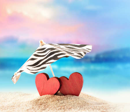 Two hearts under umbrella on the summer beach