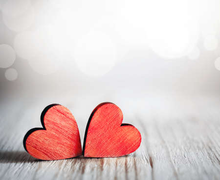 Valentines day background with two red hearts on wooden background