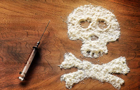 detrimental: Drug powder cocaine in the silhouette of the skull and syringe Stock Photo