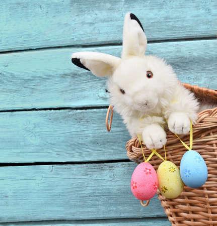 osterhase: Glücklicher Osterhase im Korb und Eier auf blauem Holzuntergrund.