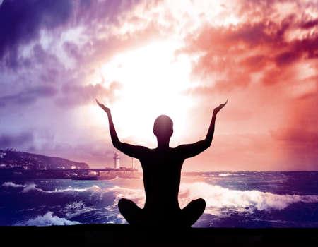 cielo y mar: Silueta mujer joven a practicar yoga en la playa al atardecer.