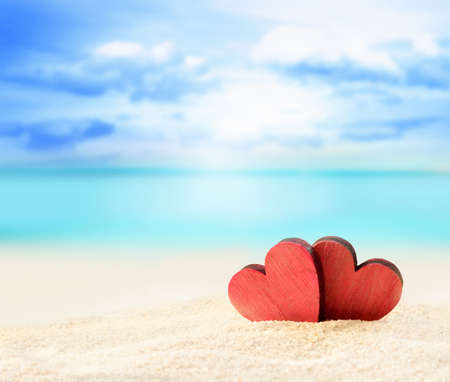 Two red hearts on the summer beach