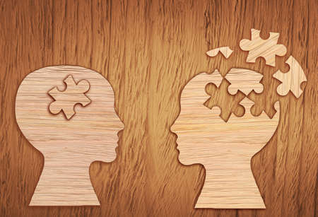Human head silhouette with a jigsaw piece cut out on the wooden background, mental health symbol. Puzzle.