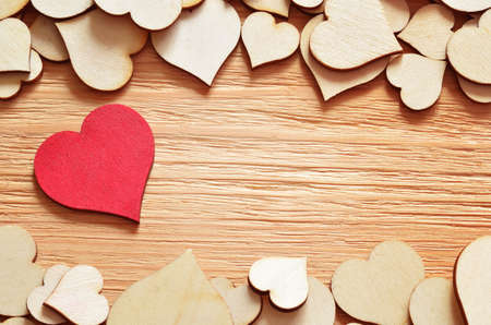 natural love: red heart on background created from a beautiful brown hearts on the wooden board Stock Photo