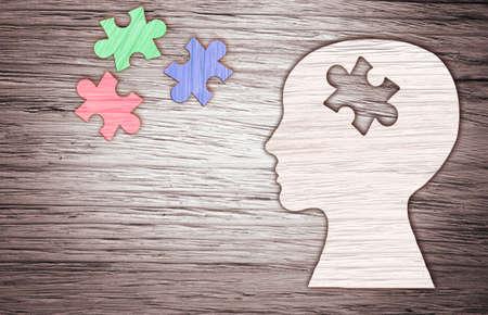 silhouette testa umana con un pezzo di puzzle tagliato su sfondo in legno, simbolo della salute mentale