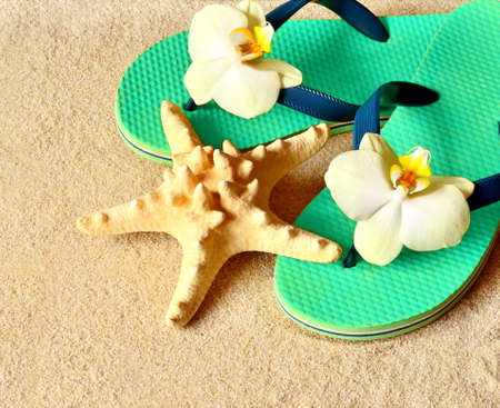 Flip Flops in the sand with starfish and orchid flowers. Summertime on beach concept. Summer beach. Stock Photo
