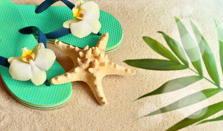 white sand beach: Flip Flops in the sand with starfish and orchid flowers. Summertime on beach concept. Summer beach. Stock Photo