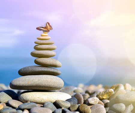 evenwicht stenen en vlinder op het strand