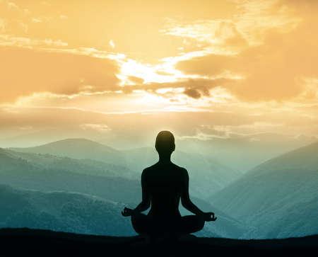 Yoga silhouette sur la montagne dans les rayons du soleil de l'aube