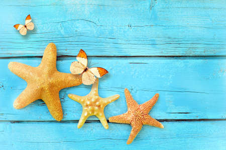 beach butterfly: Summer beach. Starfish and butterfly on the blue wooden background.Summertime. Summer concept. Stock Photo