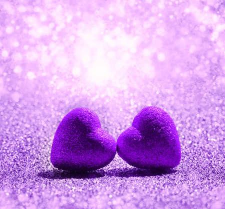 De paarse harten op abstracte lichte glitter achtergrond in liefde concept voor Valentijnsdag Stockfoto