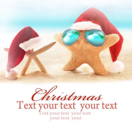 Two starfish on summer beach and santa hat. Merry Christmas Stock Photo