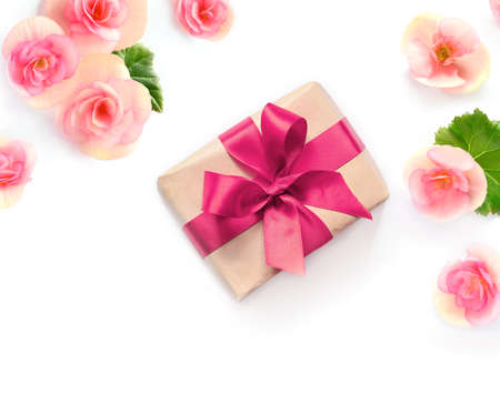 gift box with red ribbon and bow on white decorated with flowers background. flat lat, top view
