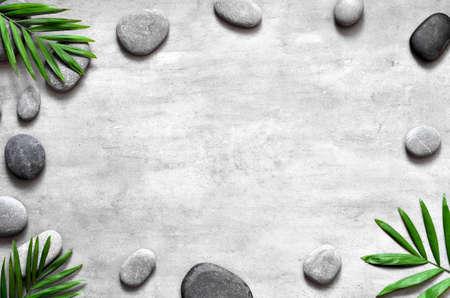 Fondo de spa gris, concepto de spa, hojas de palma y piedras grises, vista superior