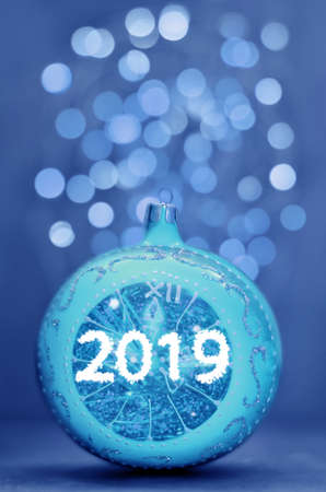 Blue glitter ball on blue background. Christmas and 2019 new year card. 免版税图像