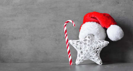 Christmas decor star with santa hat. Gray background.
