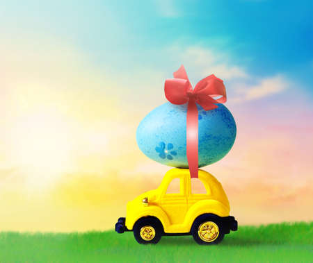 Retro toy car with Easter egg on the roof. on spring background Easter concept. Happy Easter. Stock Photo