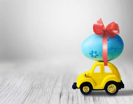 Easter egg and toy car on grey background, happy easter day concept.