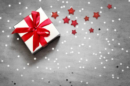Gift box with red ribbon on grey background with star. Top view.