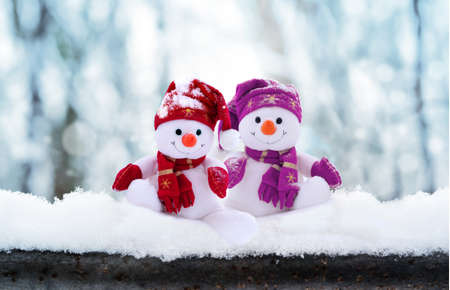 Two little snowmen the girl and the boy in caps and scarfs on snow in the winter. Festive background with a funny snowman. Christmas card, copy space.