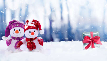Funny two snowmen with gift box in the winter scenery.Christmas decoration.