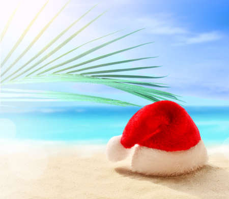Christmas holidays concept. Santa Claus hat on summer sand beach. Palm branch.