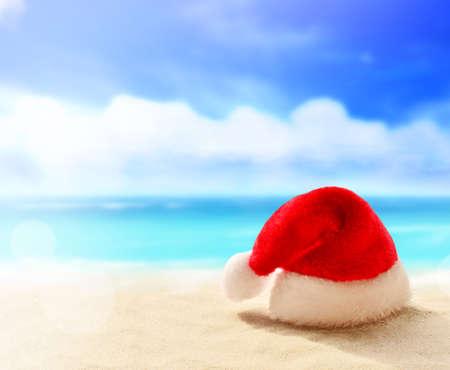 Christmas holidays concept. Santa claus hat on summer sand beach. Stock Photo