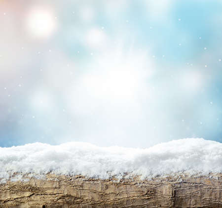 Winter background with snow and blur abstract lights. Empty wooden plank. Copyspace for text