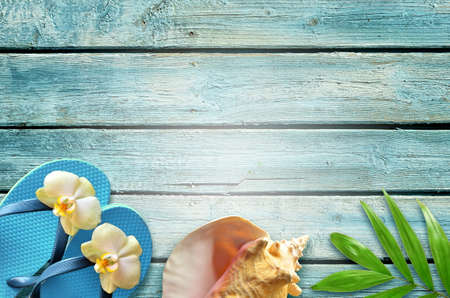 Summer flat lay background. Tropical palm leaves, flip flops and flower on old blue wooden background.