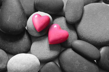 灰色の小石の背景に赤いハート。バレンタインデー。