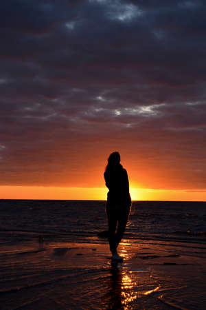 The silhouette of a girl in the sunset by the sea.