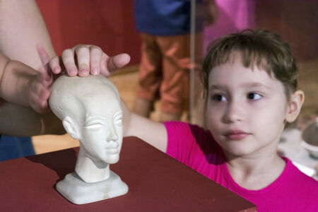 SZEGED, HUNGARY - AUGUST 17. 2014 - a girl is touching a statue in the Egyptian exhibition in Mora Ferenc Museum in Szeged Editorial